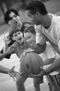 Photo of two men and two boys playing basketball.